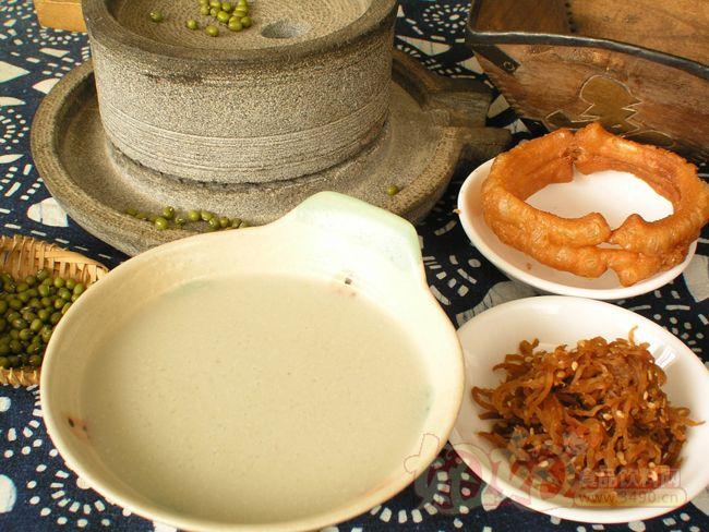 豆汁儿是北京独有的一种吃食儿。据说,豆汁儿是无意中发现的,当年有人专做绿豆粉,有一天,磨出来的豆汁儿没用完,放到第二天已经发酵了,掌柜的觉得弃之可惜,尝了一口,竟然发现酸中带甜,煮熟之后味道鲜美,从此,豆汁儿跻身为京城小吃的行业。豆汁儿产生的具体时间已无从考证,据记载,乾隆十八年,有人上殿奏本称近日新兴豆汁一物,已派伊立布检查,是否清洁可饮,如无不洁之物,着蕴布招募豆汁匠二三名 ,派在御膳房当差,如此算来,北京人喝豆汁儿至少有二百多年的历史了。 很多不了解豆汁儿的人,都以为豆汁儿就是豆浆,其实不然,它实