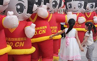 漯河食品博览会上两个小女孩在和好妞妞玩耍