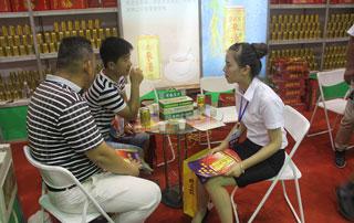 常老实工作人员在2015年秋季郑州糖酒会现场与客户交流